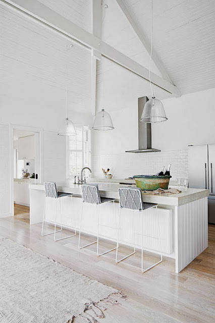 White kitchen with high ceilings and exposed beams