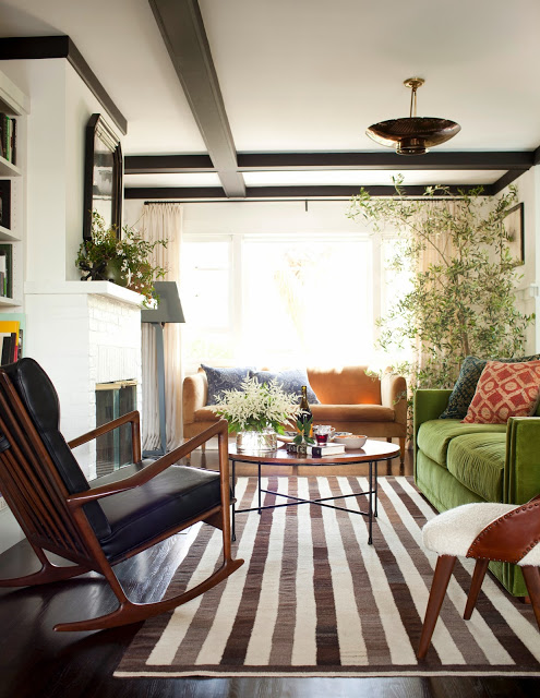Living room with a striped rug, green sofa and exposed ceiling beams