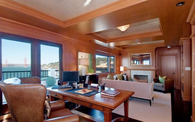 wood paneled home office/library with a tile fireplace, sofa and a view of the Golden Gate Bridge