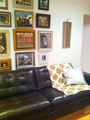 COCOCOZY Gate throw in tan on a dark brown leather sofa in front of a wall full of framed pieces of art in a readers home