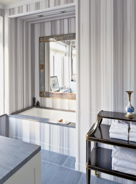 Modern bathroom in Kitchens and Baths by Michael S. Smith with striped marble walls and step in tub and a tile floor