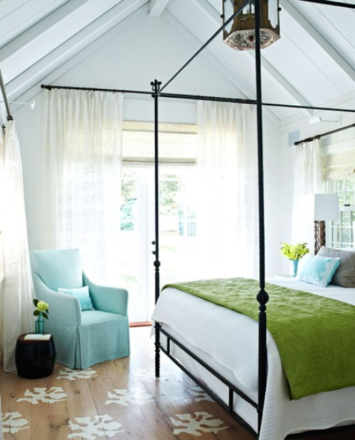 Bright bedroom with an iron canopy bed with white bedding and a bright green blanket draped across the foot of the bed, blue Holly Hunt armchair with a Leontine Linens boudoir pillow, painted reclaimed wood floors and breezy white floor length curtains