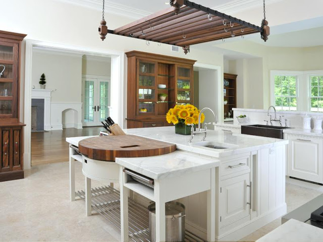 white kitchen with farmhouse sink, island and wood cabinets and hanging pot rack
