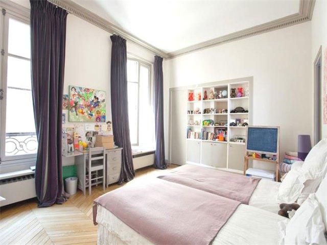 Bedroom with purple curtains and herringbone wood floor