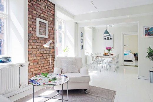 Alternative view of the living room's where you can see the painted, round coffee table, a white armchair, an exposed brick wall with an empty picture frame and the dining room