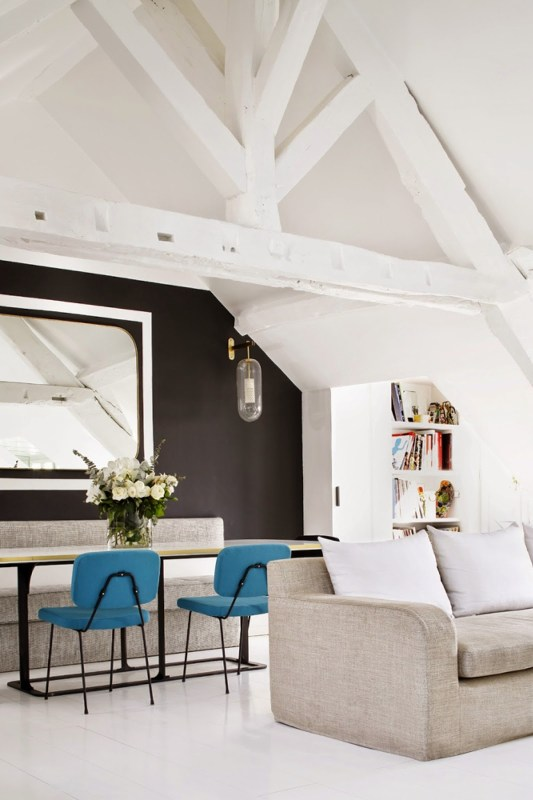 Open plan living room in a Paris attic apartment with black accent wall