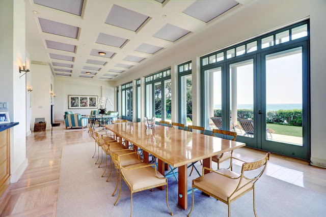 dining room with high coffered ceiling with a long wooden table surrounded by yellow chairs with glass doors and windows with an ocean view