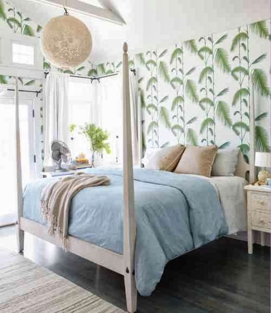 Beachy bedroom with a white four poster bed and floor to ceiling palm inspired wallpaper
