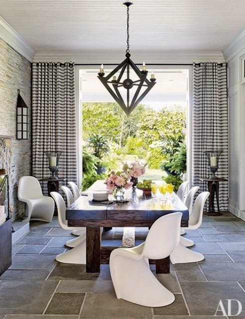Dining room with stone tile floor and white Panton chairs