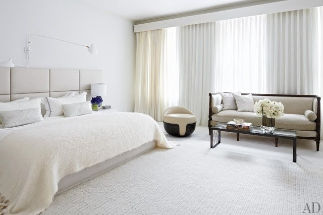 White bedroom with upholstered headboard, picture window and a high back sofa