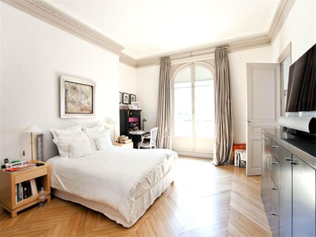 Bedroom in a Paris apartment with herringbone wood floor
