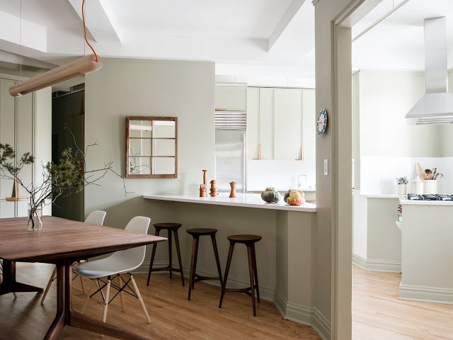Kitchen overlooking dining room with greige walls and cabinets and wood accents