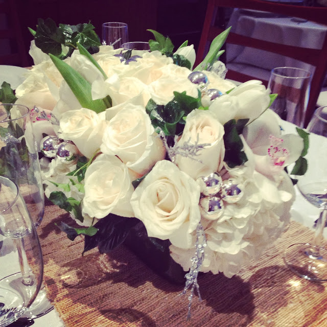 Holiday centerpiece with white and green roses, tulips, ivy, hydrangeas and silver ornaments