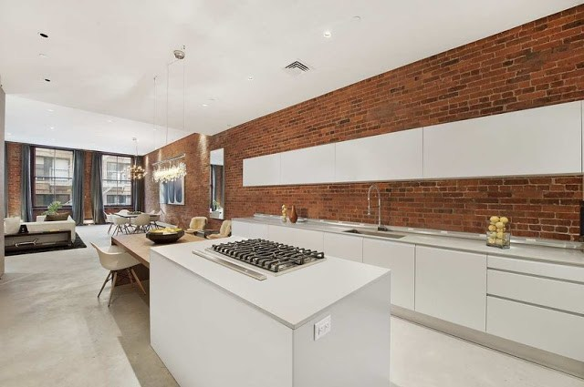 modern, sleek and white open kitchen with exposed brick walls and concealed appliances