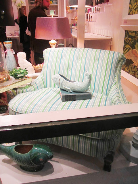 colorful blue, green and white striped settee in the window with a ceramic fish dish