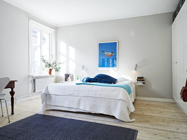 bedroom in a tiny apartment with blue rug, light wood floors, grey walls, a floating nightstand with wall mounted lights