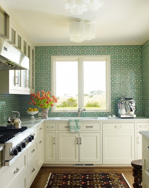 A white kitchen with aqua mosaic tiles from counter to ceiling backsplash, wood floors and stainless appliances