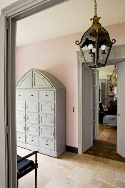 Pink and grey foyer in a French mansion with stone tile floor, lantern light, double doors leading to the living room and an arched cabinet