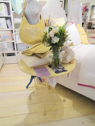 Close up of the night table in Serena & Lily's bright vignette. The night stand is round and yellow with wire legs and it holds a glass jug of flowers, a stuffed rabbit, two yellow purses and a yellow and white pillow.