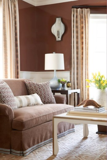 Family room with brown walls, a brown sofa with brown and white accent pillows and a light wood coffee table