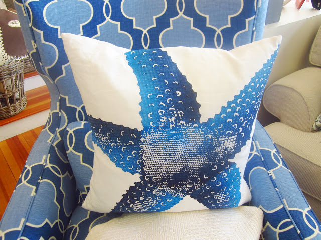 close up of white pillow with a blue starfish printed on it and the arm chair