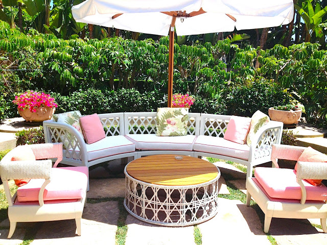 Outdoor sitting area white outdoor lounge chair with white cushions with pink piping round woven coffee table umbrella