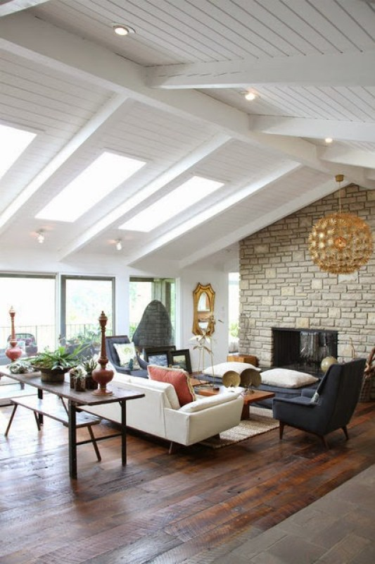 Living room with stone fireplace, skylights and rustic wood floor