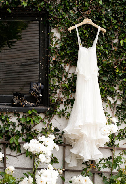 white Chloe gown hangs on a trellis of roses in a garden