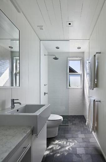 Classic meets modern in a bathroom with white paneled ceiling, flagstone tile floor, marble sink and counter top, drawers with long pulls, and shower with an overhead shower head, white tile backsplash and floor length glass door