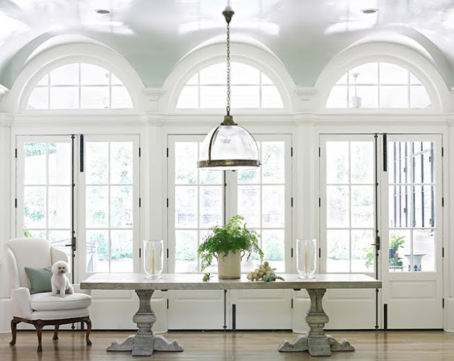 foyer with light blue lacquer arch windows, a dome pendant light, a long stone table and a white armchair