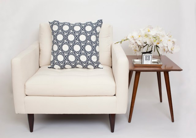 COCOCOZY pillow on a white armchair next to a wooden table holding orchids and a COCOCOZY candle