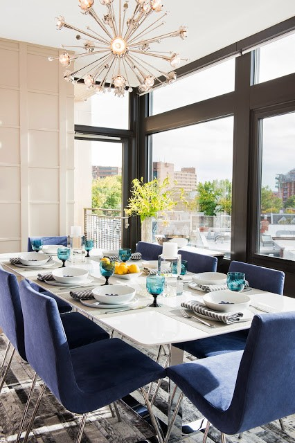 Close up of a modern dining room with custom cobalt blue upholstered Pierre Paulin chairs