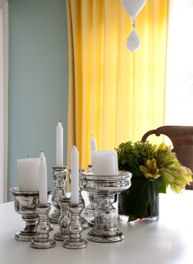 Teresa's Green paint in a dining room with yellow curtains, a white table and wood chairs. On the table is an assortment of mercury candle stick holders