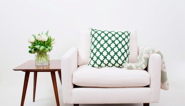 White armchair with COCOCOZY pillow and COCOCOZY throw draped over the arm next to a wood side table with a glass vase holding white tulips