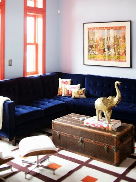 Living room with a Louis Vuitton trunk doubling as a coffee table and a blue velvet sectional sofa