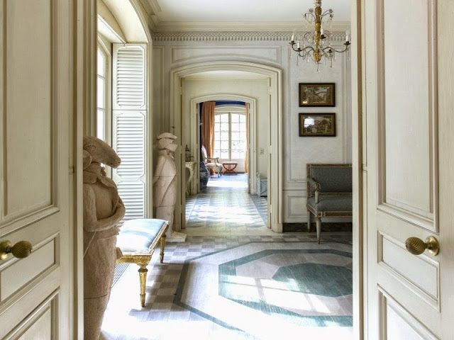 Front hall of a NYC townhouse with painted wood floors leading to an enfilade