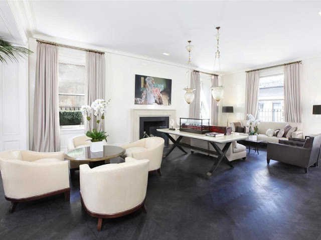 Living room in an apartment with grey herringbone wood floors, fireplace with white and grey marble mantel, floor length drapes, dueling sofas with two armchairs and four white armchairs surrounding a small round table with orchids