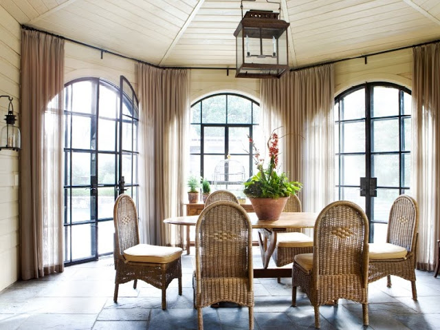 Sunroom with arched windows, a stone floor, wicker dining chairs, a lantern like chandelier and sconces
