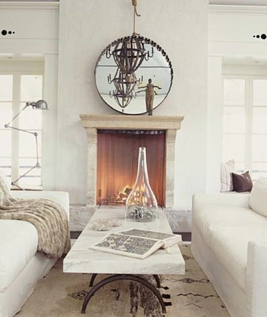 living room with dueling sofas, a marble top coffee table separating them, a fireplace with a round mirror on the mantel reflecting a metal chandelier