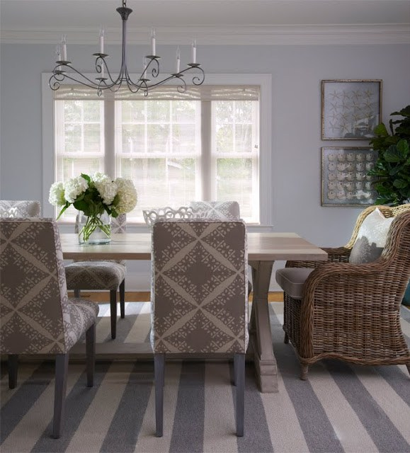 Dining room with a striped grey and white rug, upholstered chairs around a farmhouse style table with a wicker armchair at the head of the table