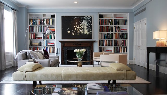 jarlath mellett's living room fireplace suround by a wood mantel, built in bookshelves filled with books, a grey sofa, neutral cushioned bench and dark wood floors.