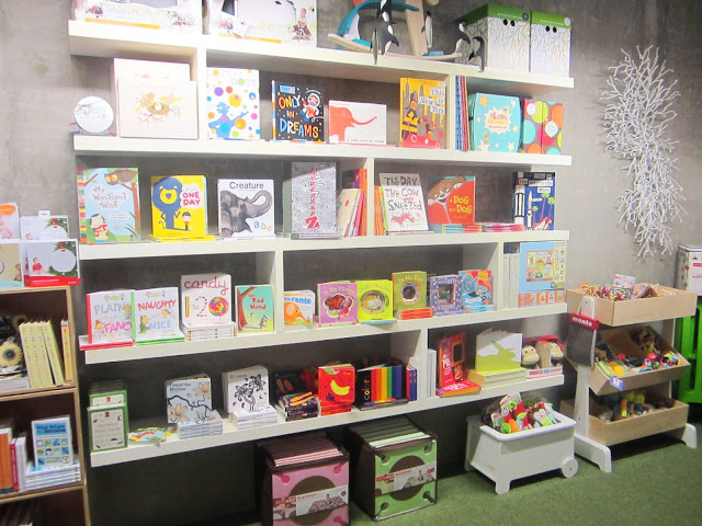 Floating shelves in Tottini's store holding children's books