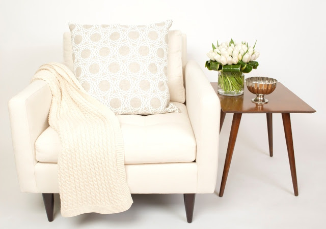 COCOCOZY Pillow on a white armchair with a cable knit throw and a wooden side table