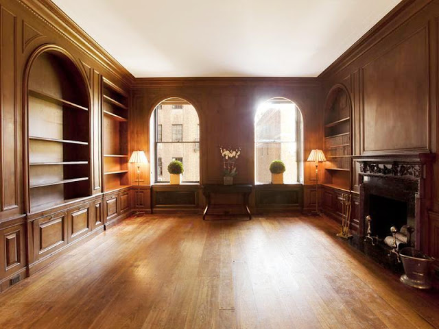 Wood paneled library with arched windows, wood floor and fireplace
