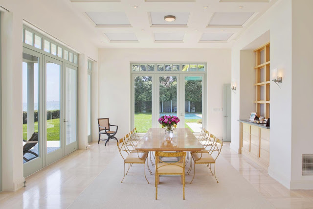 open plan dining room with yellow metal chair surrounding a wood table, high ceilings and windows that offer fantastic views of the pool in the backyard as well as the ocean