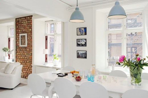 Dining room with blue pendant lights, large windows, white table and chairs
