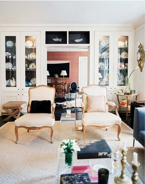 Living room with dark floor, Lucite coffee table, two upholstered Louis XIV chairs and white cabinets with glass doors