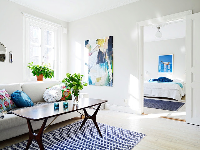 Bright white living room in a tiny apartment with a view into the bed room