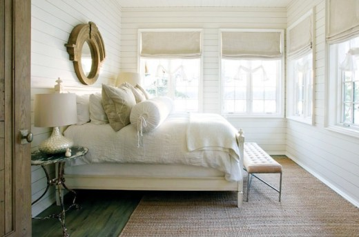 Rustic bedroom with white beadboard walls, a stained wood floor, sea grass rug, four windows with roman shades, an ottoman at the foot of the bed and a round mirror above the bed