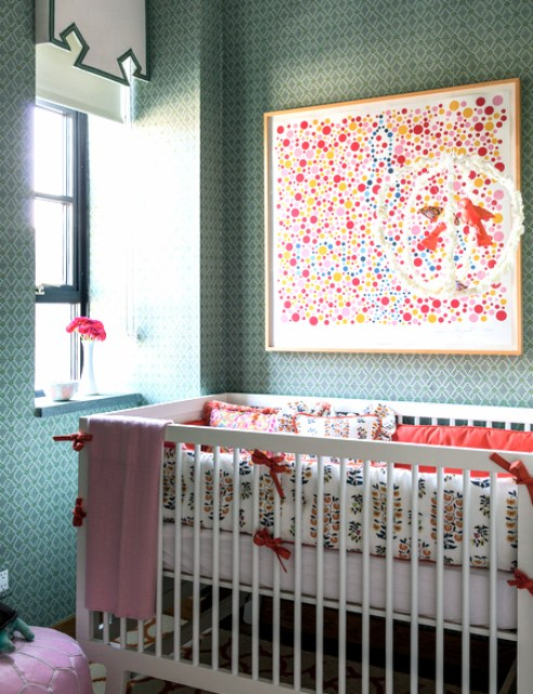 nursery with white crib with white bedding with an orange and blue pattern. The walls are covered in a green, triangle print wallpaper with a piece of modern art made of different colored dots on the wall.